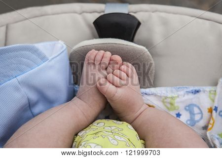 Chubby feet of a newborn baby boy in  stroller while on a walk outside in the street