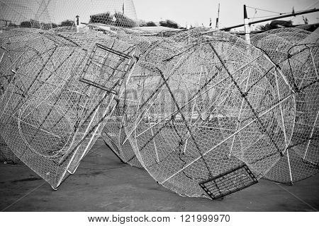 Metal fishing nets in a port. Horizontal bw toned shot