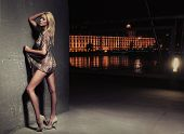 stock photo of seductress  - Sexy young blonde beauty posing over night city background - JPG