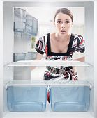stock photo of eatables  - Young woman looking on empty shelf in fridge - JPG