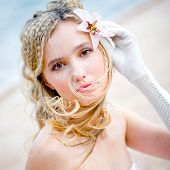 Face of beautiful delicate bride with lilly in hair, square portrait in pastel colors