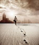 stock photo of footprints sand  - man walking in a desert towards a city - JPG