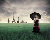 Beautiful woman with umbrella standing on a green meadow with landmarks from different cities on the