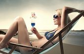foto of woman beach  - Beautiful woman lying on a deckchair with a cocktail in her hands - JPG