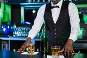 Two glasses of whiskey on bar counter and bartender standing in background poster