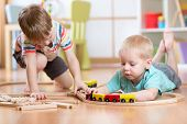 Cute children playing with wooden train. Toddler kids play with blocks and trains. Boys building toy poster