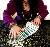 stock photo of fortune-teller  - card reader with cards in purple hands and body only
