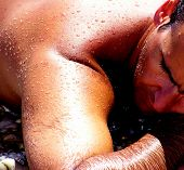pic of sun-tanned  - man laying on the beach focus on wet sun tanned skin - JPG