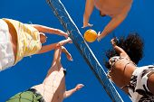foto of volleyball  - Players doing summer sports trying to block a dangerous attack in a beach volleyball game - JPG