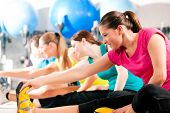 stock photo of stretching exercises  - Group of four people in colorful cloths in a gym doing aerobics or warming up with gymnastics and stretching exercises - JPG