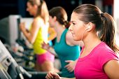 Running on treadmill in gym - group of women exercising to gain more fitness, the woman in front wea