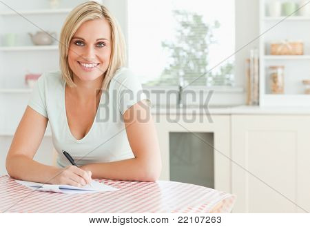 Charming woman proof-reading a text looks into camera in the kitchen