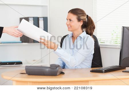smiling businesswoman receiving a pile of paper in her office
