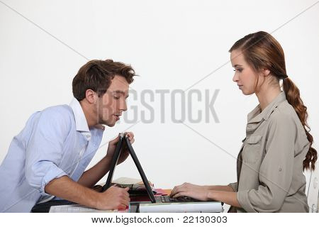 Man helping lady with laptop