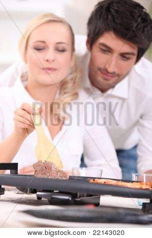 Couple cooking surf and turf on a tabletop hotplate