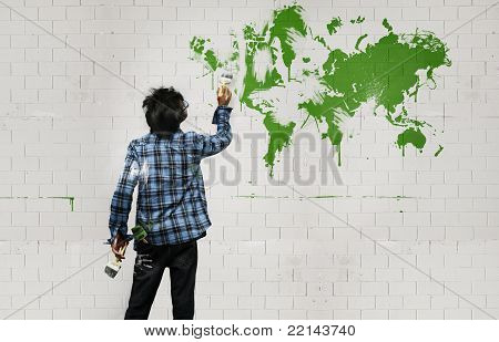Young Boy Painting On A Brick-wall