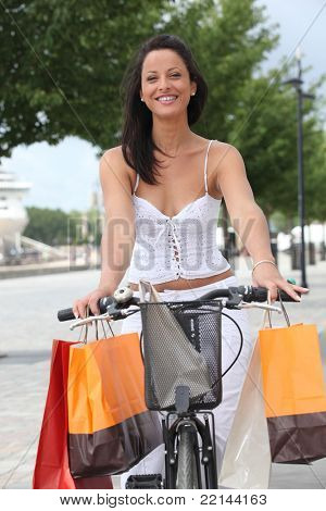 Woman on a pushbike laden down with store bags