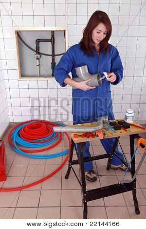 Female plumber gluing pipe together
