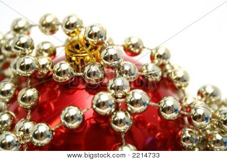 Red Glass Sphere And Celebratory Beads On A White