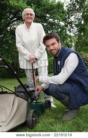 Senior with gardener and lawnmower