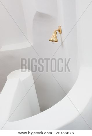 Small golden lamp an a white rough wall