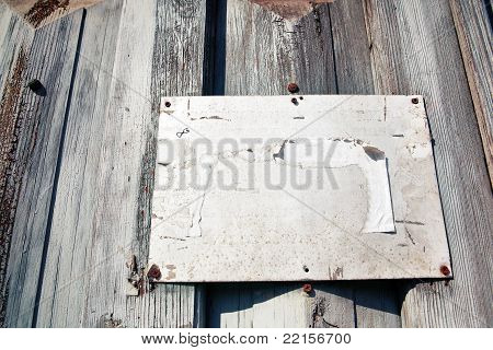 Blank metal board on grungy wooden background