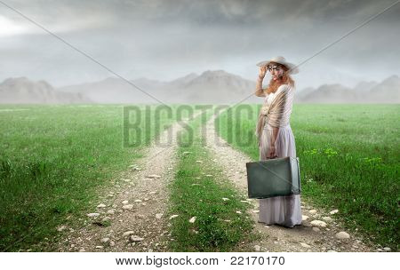 Beautiful woman carrying a suitcase on a countryside road