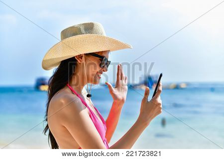 poster of Swimsuit Concept. Beautiful girl wearing a swimsuit playing mobile on the beach. Beautiful girl is traveling on the beach. Beautiful girls are happy.