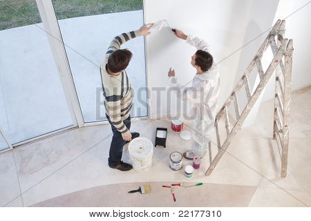 Young man showing a spot on the wall to painter