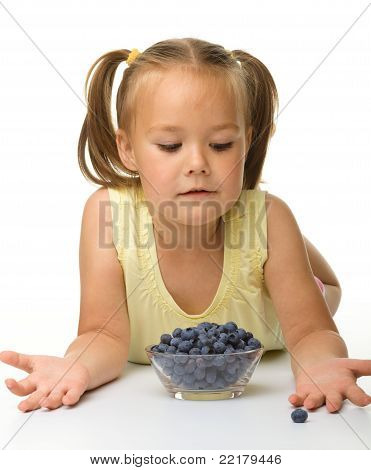 Cute Little Girl Is Eating Blueberry