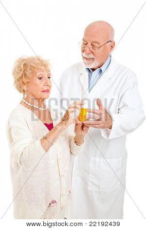 Senior woman questions the pharmacist about her prescription medication.  Isolated on white.