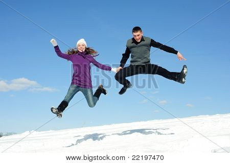 Jumping pair isolated snow field and blue sky