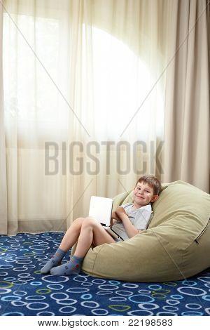 Kleiner Junge mit Laptop, Lächeln, Blick in die Kamera.?