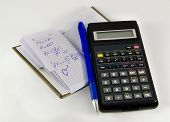 Notebook with chemical and physical equations with blue pen and a calculator. Over white.