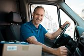 Delivery man driving van with packages on the front seat. Happy mature courier in truck. Portrait of poster