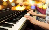 music, musical instruments and people concept - close up of woman hands playing piano over lights ba poster
