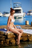 Elegant sexy woman in the white bikini on the sun-tanned slim and shapely body is posing poster