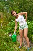 foto of frazzled  - Young woman holding watering pot in kitchen - JPG