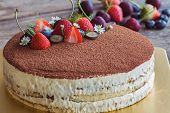 Round Tiramisu Cake On Wood Table Sprinkle With Cacao Powder And Decorated With Fresh Fruits. Italia poster