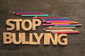 Text Stop bullying on wooden background poster