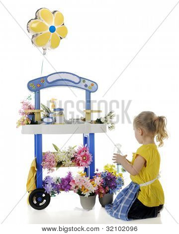 A preschooler tending the flowers on her vending stand.  Signs on the stand left blank for your text.  On a white background.