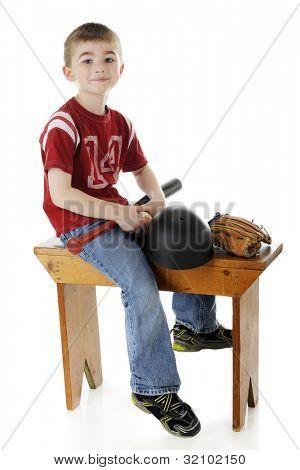 Elementare junge glücklich gebietsübergreifenden eine Umkleide-Bank mit seiner Fledermaus, Ball, Schutzhelm und