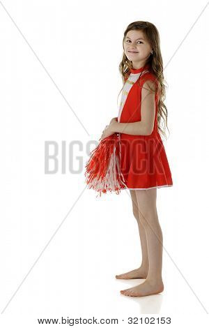 A pretty elementary cheerleader in her red and white uniform.  On a white background.
