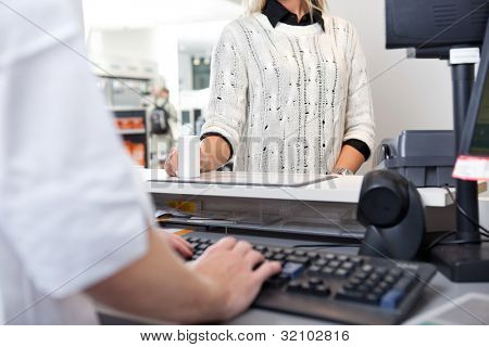 Mid-section of customer standing at checkout counter in drugstore