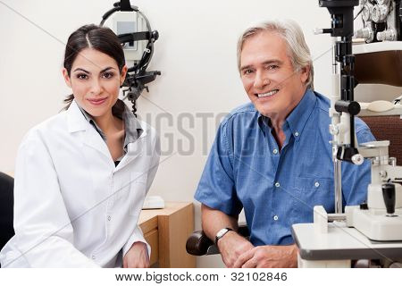 Confident female optometrist smiling with patient in her clinic