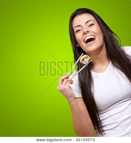portrait of young woman holding sushi against a green background