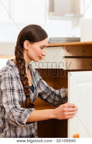 Junge Frau ist einen Schrank montieren, da sie innen oder heraus bewegt