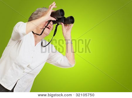 portrait of a senior woman looking through binoculars over a green background