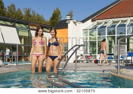 Two happy young women wading water in hydrotherapy in a health spa