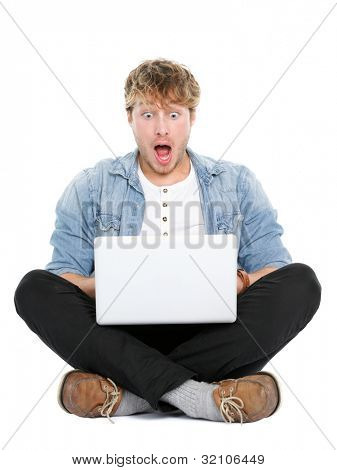 Laptop computer man shocked looking surprised at screen. Young modern male student model sitting cross legged on floor isolated on white background.